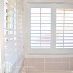 Aluminium shutters on a bathroom corner window