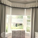 Trimmed box pleat valance with roller blinds & side drapes on a bay window