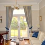 Blue & beige blockout curtains with tiebacks on brass rod with rings