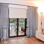 Silver sheer curtains on a black rod with Ivory blockout roller blinds