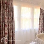 Red & beige blockout curtains with white sheer on a silver rod