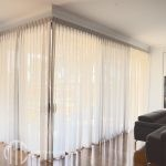 Grey box pleat sheer curtains on corner window
