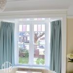 Short aqua box pleat curtains in a bay window