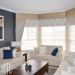 Double roman blinds with pelmets and side drapes on a bay window