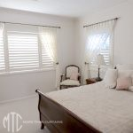 Ivory trellis pattern sheer curtain on metal rods with rosette holdbacks over painted hardwood plantation shutters