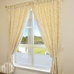 Cream damask patterned goblet Pleat curtains on a hand painted timber rod with tassel tiebacks