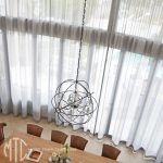 Double-storey s-fold silver sheer curtains on a curved window