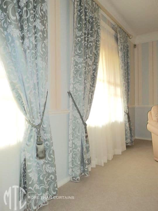 Blue scroll pattern blockout curtains with tassel tiebacks & ivory sheers on painted timber rods