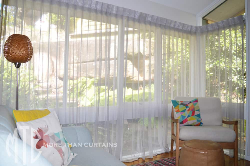 Grey box pleat sheer curtains on corner window