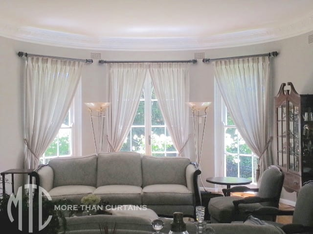 Grey sheer pinch pleat curtains on painted timber rods with tassel tiebacks