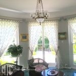 Ivory trellis pattern sheer pinch pleat curtains on painted timber rods with tassel tiebacks