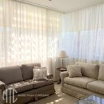 Ivory sheer curtains on a corner window