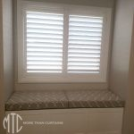 Painted hardwood plantation shutters with beige trellis pattern window seat