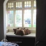 Painted hardwood plantation shutters on a recessed bay window