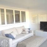 Painted hardwood plantation shutters as a room divider