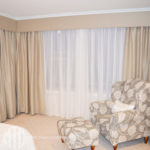 Beige blockout curtains with matching pelmets & white sheers on a bay window