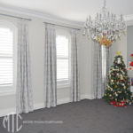 Grey damask velvet box pleat curtains on grey painted timber rods over arched windows