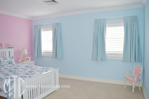 Girl's blue box pleat curtains on white rods