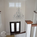 Painted hardwood plantation shutters in front entry stairwell