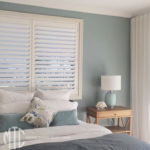 Painted hardwood plantation shutter & white sheer s-fold curtain