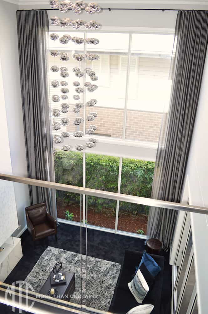 Double storey charcoal s-fold sheer curtains on a black track
