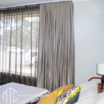 Silver blockout & bronze sheer double s-fold curtains on a corner window