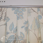 Blue & ivory floral patterned box pleat curtains on a silver rod