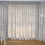 Silver sheer s-fold curtains on a bay window