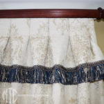 Box pleat curtain with fringed ruffle on a stained timber rod