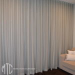Sheer aqua s-fold curtains over shutters with blockout lining