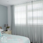Sheer aqua s-fold curtains over shutters