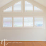 Painted hardwood plantation Shutters on a triangle window
