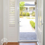 Painted hardwood plantation shutters beside front door