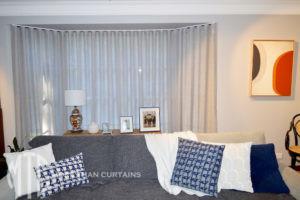 S-fold silver sheer curtain in a bay window