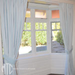 Box pleat baby blue curtains on a bay window with tiebacks