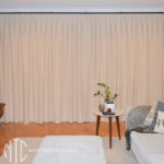 Box pleat beige curtains on a black rod