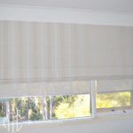 Beige striped Roman blind with coordinating screen roller blinds