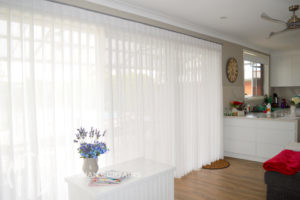 Box pleat white sheer curtains on a silver rod