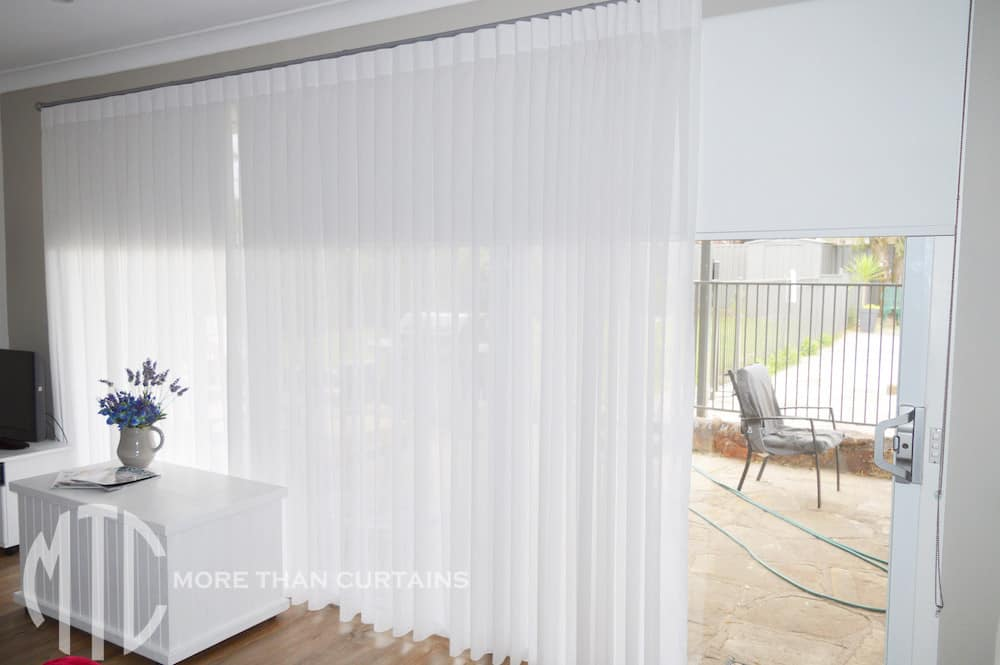 Box pleat white sheer curtains on a silver rod with white blockout roller blinds