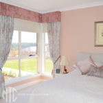 Pink & grey floral curtains with blush pink velvet pelmet & tiebacks on a corner window