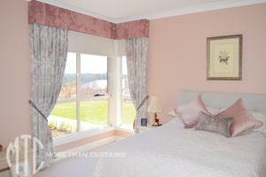 Pink & grey floral curtains with blush pink velvet pelmet & tiebacks on a corner window