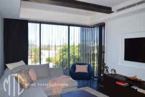 Black sheer s-fold curtains on a corner window