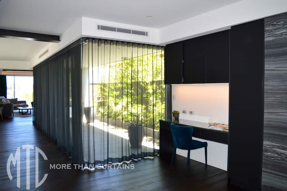Black sheer s-fold curtains on a corner window
