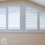 Painted hardwood plantation shutters on a shaped window