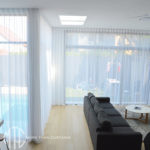 S-fold sheer white curtains on tall windows