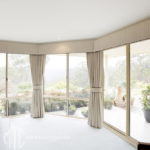 Beige blockout curtains, pelmets & tiebacks with contrast piping on a bay window