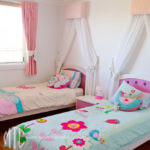 Kids' pink curtains with white bow tiebacks & bed canopy