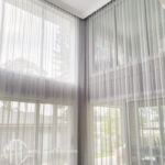 Two-storey white sheer curtains on a corner window