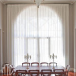 White box pleat curtains on a black rod on an arched window