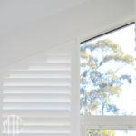 Painted hardwood plantation shutters on a triangle window